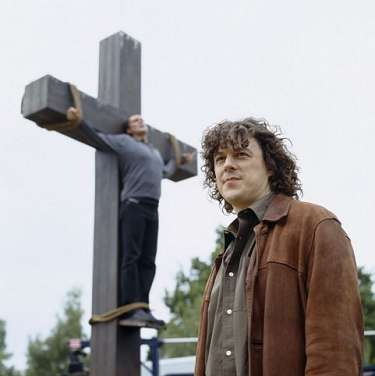 A publicity shot, JOnathan with Adam in the background attached to a cross